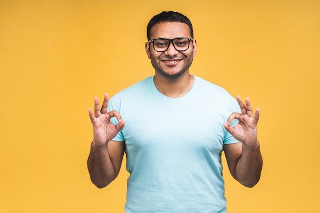 黄色の背景の上に孤立したアフリカ系アメリカ人のインドの黒人男性は、手と指でokサインをしてポジティブに笑っています。成功した表現。