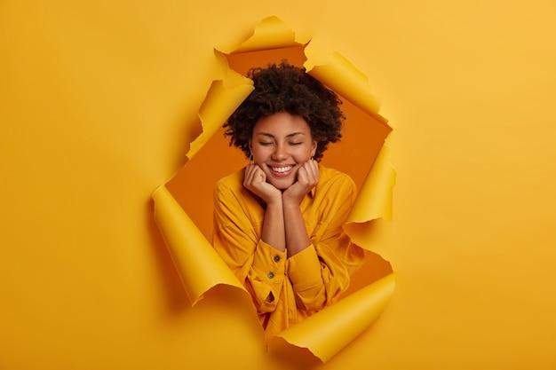 アフロアメリカンの楽しい女性は、楽しいコミュニケーションを楽しんで、広く笑顔で、両手をあごの下に持ち、目を閉じて立っています