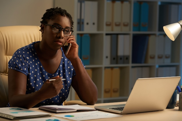 Afro-american lady sitting at desk in office at night and talking on mobile phone
