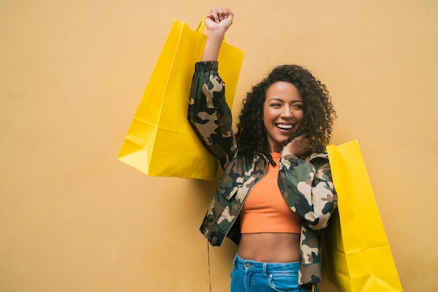 Afro american latin woman holding shopping bags.