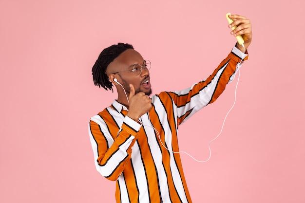 아프리카계 미국인 남성 블로거는 팔로워와 이야기하고 스마트폰 카메라에 포즈를 취하는 엄지손가락을 보여줍니다.