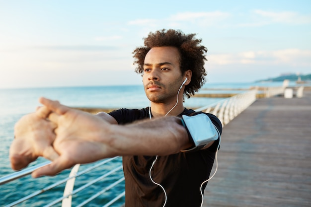Afro-american male runner with beautiful athletic body and bushy hair stretching muscles, raising his arms while warming up before morning workout session.