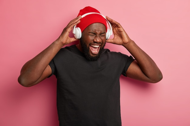 Afro american man enjoys music player or audio record, keeps hands on headphones, has fun while listens popular songs, isolated on pink wall.
