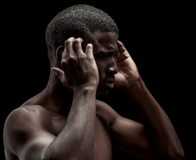 Afro-american man feels headache or stress. profile portrait of naked dark-skinned man expressing exhaustion.