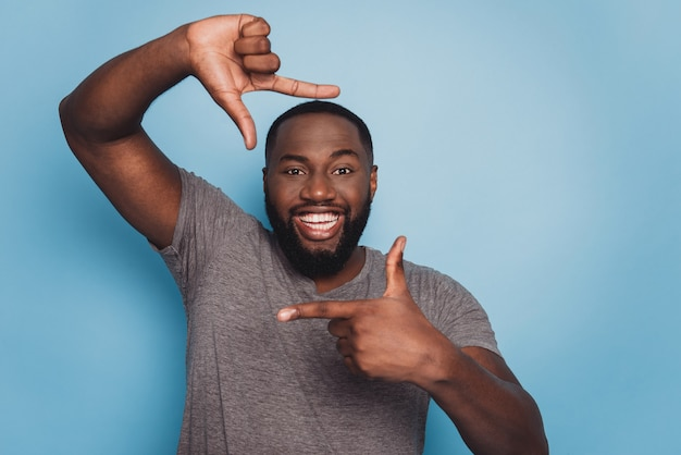 Afro american man framing photograph fingers over blue background