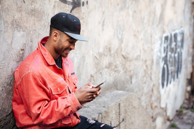 Afro american man in hat typing message on mobile phone