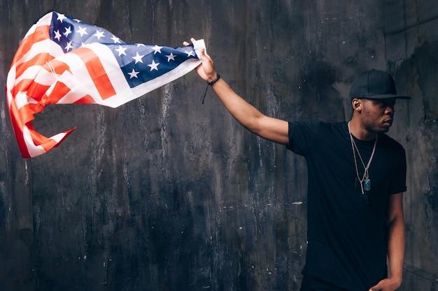 Афро-американский мужчина держит в руке под флагом сша на темном фоне
