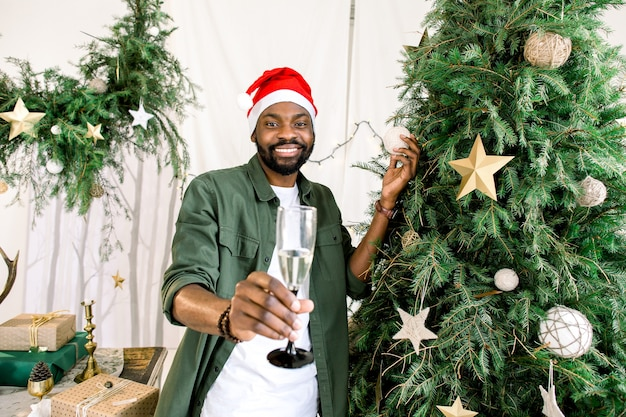 Afro american man holding champagne near christmas tree