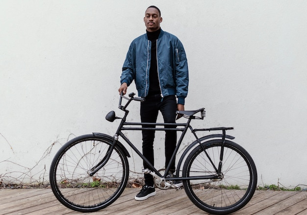 Афро-американский мужчина держит велосипед перед ним