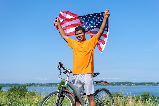 Afro american man holding and waving usa flag and standing with bike