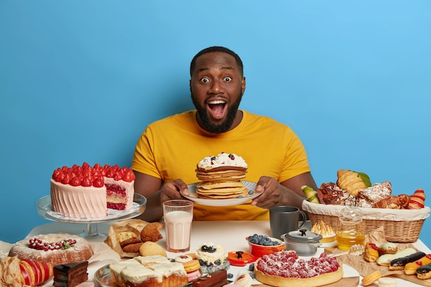 Afro american man holds plate with creamy pancakes and berries, keeps mouth opened, has surprised expression, dressed in casual yellow t shirt