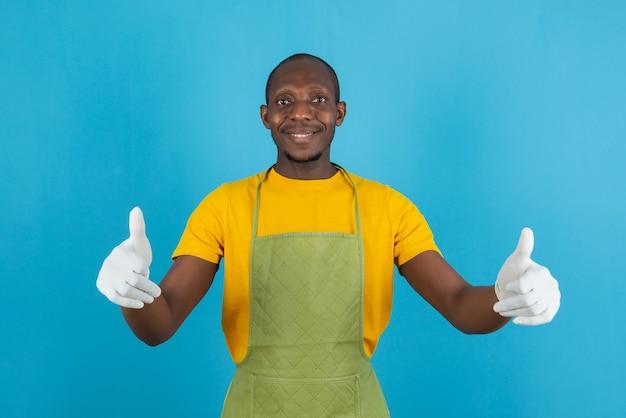 青い壁に親指をあきらめて保持している緑のエプロンでアフリカ系アメリカ人の男