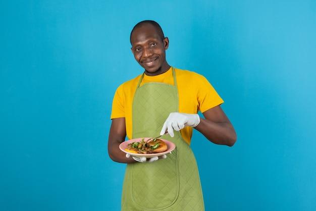 青い壁に食べ物のプレートを保持している緑のエプロンのアフロアメリカ人