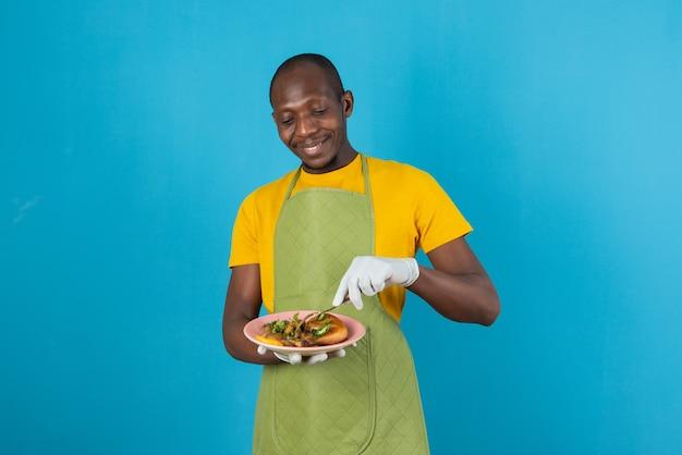 Афро-американский мужчина в зеленом фартуке держит тарелку с едой на синей стене