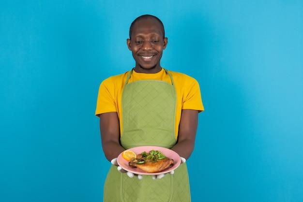 Афро-американский мужчина в зеленом фартуке, предлагающий тарелку с едой на синей стене