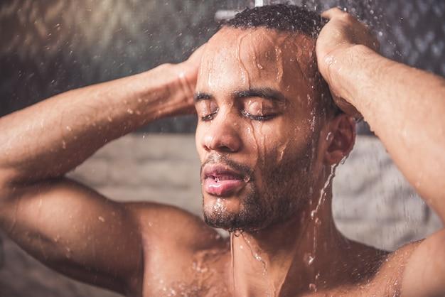 Afro american man is taking shower in bathroom.