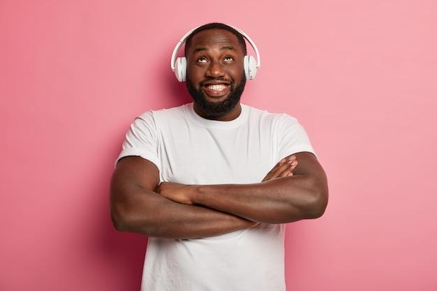 아프리카 계 미국인 남자는 팔짱을 끼고 위를 바라보고 음악을 듣기 위해 스테레오 액세서리를 착용하고 재생 목록에서 좋아하는 노래를 즐기고 실내에서 즐겁게 지냅니다.