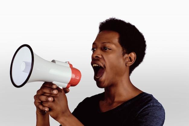 メガホンで叫んでいるアフロアメリカ人。