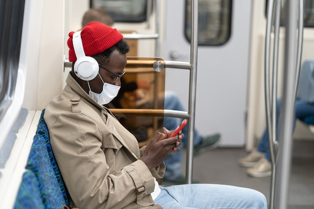 Afro-american man in subway train, wear face mask, using mobile phone, listens to music