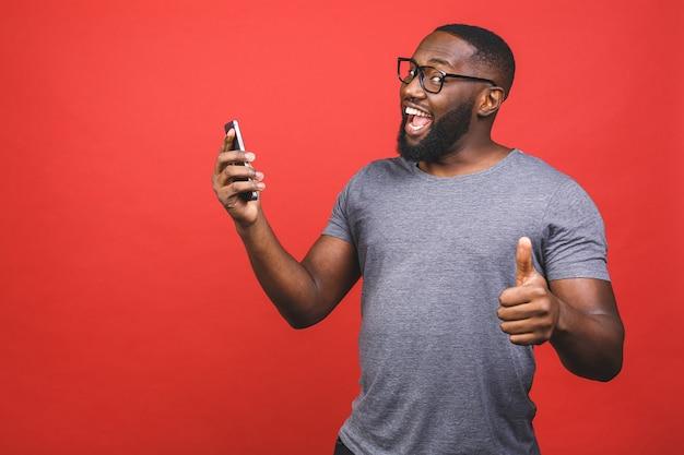 スマートフォンを使用してokの標識、指で親指を上げて笑顔で幸せなアフロアメリカンの男