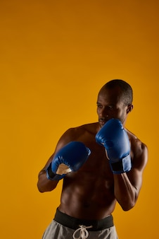 Afro american man with bare torso is wearing boxing gloves