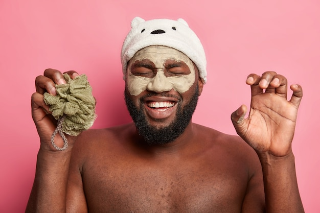 Afro american man with clay mask, expresses positive emotions isolated