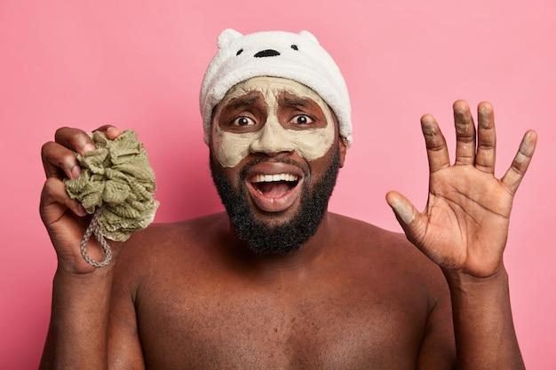 Uomo afroamericano con maschera all'argilla, esprime emozioni positive isolate