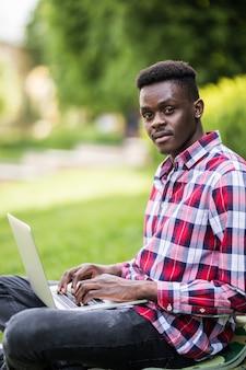 都市公園の芝生の上のラップトップを持つアフロアメリカンの男
