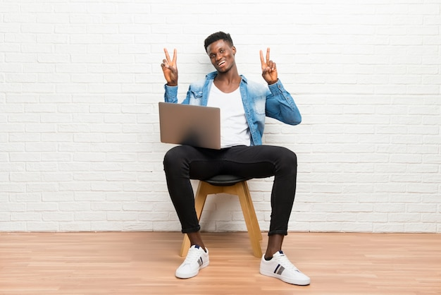 Afro american man working with his laptop smiling and showing victory sign
