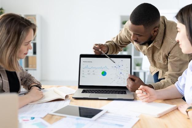 Афро-американский маркетолог, указывая на экран ноутбука, сообщая на встрече маркетинговую статистику