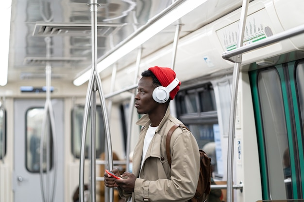 Afro-american millennial man in subway train, using mobile phone, listens to music with wireless headphones in transportation