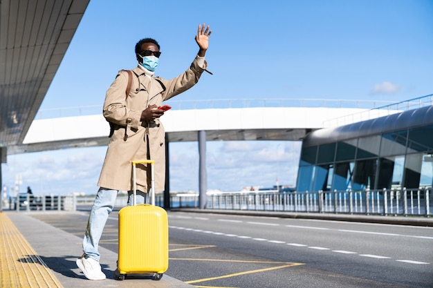Afro-american millennial man with yellow suitcase stands in airport terminal, using phone, calling taxi, raising hand, wear face medical mask to protect yourself from contact with flu virus, covid-19