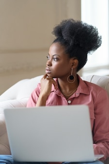 Afro american millennial woman with afro hairstyle sitting on couch taking break from work on laptop