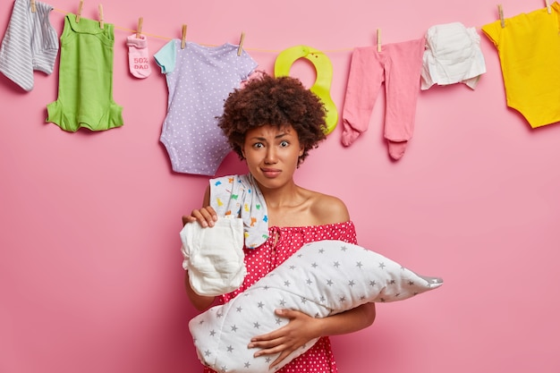 Afro american mom holds dirty diaper and feels aversion, takes acre of infant who has deep sleep at day, busy nursing newborn, stands against rosy wall, hanging washed baby clothes behind