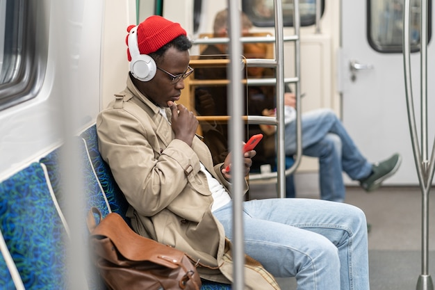 Afro-american passenger man in subway train, using mobile phone, listens to music with wireless headphones in transportation
