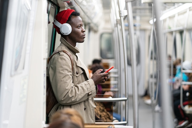 Afro-american passenger man in subway train, using mobile smart phone, listens to music with headphones