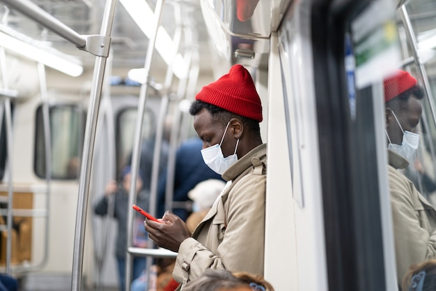 Afro-american passenger man in subway train, wear face mask to protect yourself from covid