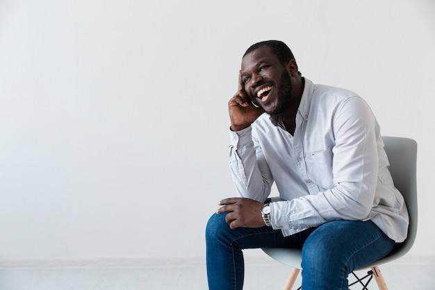 Афро-американский пациент сидит и смеется
