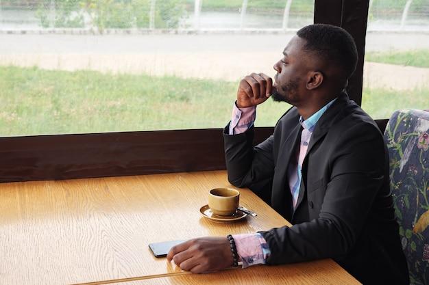 アフリカ系アメリカ人の物思いにふける疲れた青年実業家がカフェに座っています。窓を見る若い黒人男性の肖像画は彼の頭を回し、カメラを見る。ひげを生やした若い男はシャツとスーツのジャケットを着ています。