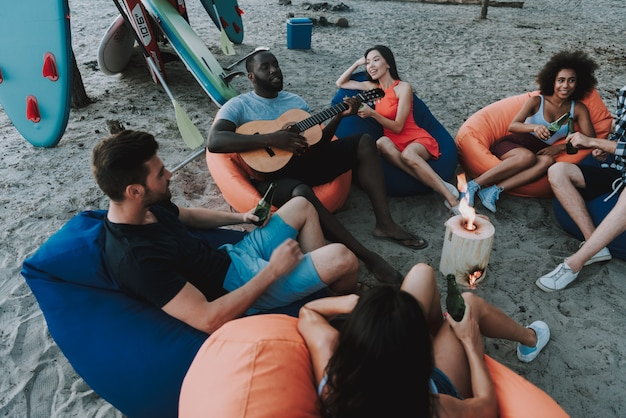Afro american people plays guitar on beach party.