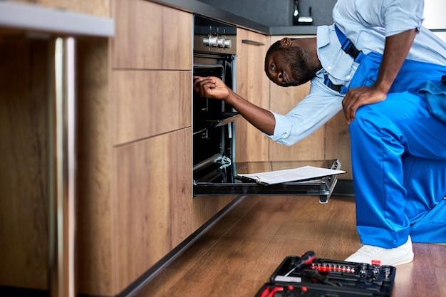 제복을 입은 아프리카계 미국인 수리공이 도구를 사용하여 부엌에서 깨진 오븐을 고치고 있습니다. 파란색 작업복을 입은 흑인 남자가 수리 중입니다. 수리 서비스 개념입니다. 측면보기 초상화