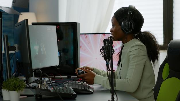Афро-американский космический стрелок счастлив после победы в виртуальном соревновании с использованием мощного компьютера с rgb-подсветкой. онлайн-трансляция кибер-выступления во время турнира по видеоиграм дома с неоновыми огнями.