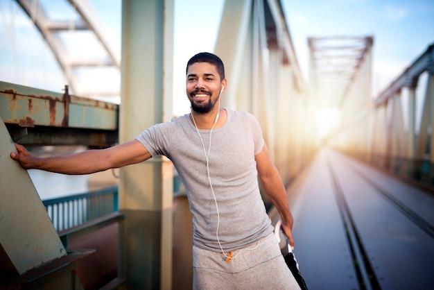 Sportivo afroamericano che riscalda il suo corpo per un allenamento all'aperto