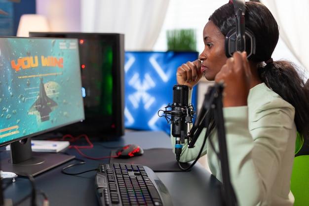 バーチャルコンペティションで優勝した後、幸せなアフリカ系アメリカ人の戦略的なスペースシューティングプレーヤー。ネオンライトを備えた自宅でのビデオゲームトーナメント中に実行するオンラインストリーミングサイバー。