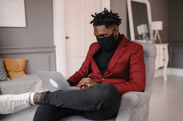 Afro american in a suit wears a black medical mask