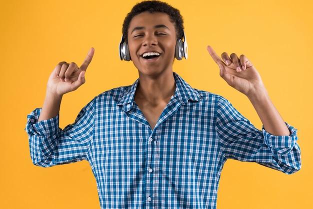 Afro american teenager in headphones is dancing.
