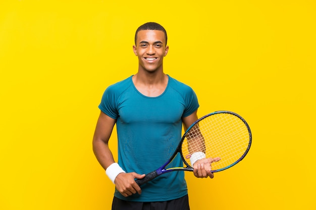 Afro american tennis player man over isolated yellow