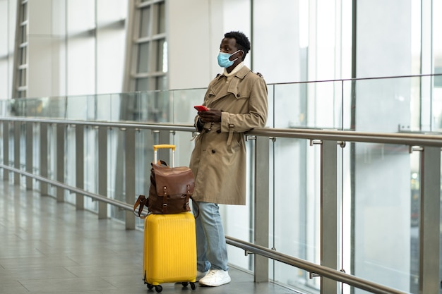 Afro-american traveler man with yellow suitcase stands in airport terminal, wear protective face mask to protect yourself from flu virus, pandemic covid-19, waiting for flight and boarding.