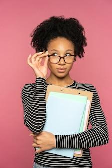 분홍색 벽에 고립 된 아프리카 계 미국 흑인 교사 또는 교사 여자