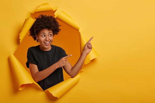 Afro american woman checks out incredible offer, points right with index fingers, suggests buying something